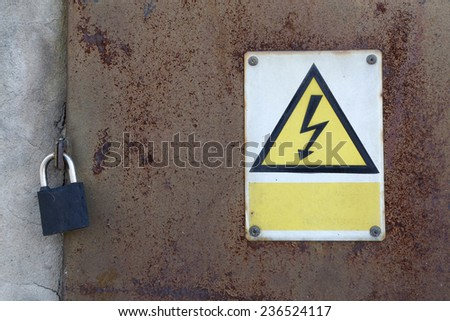 old rusty metal door and padlock and warning attention sign board and empty space to your own text - stock photo
