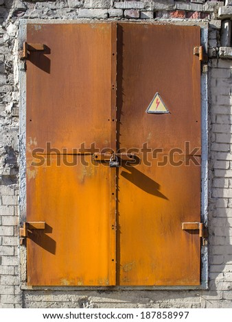 """old rusty metal door to the substation with a lock and with a """"cautiously electricity"""", illuminated sun rays directed from left  - stock photo"""