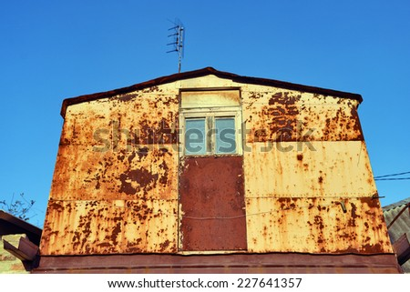 old rusty metal house with window - stock photo