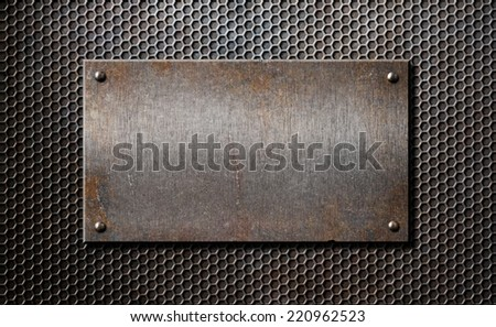 old rusty metal plate over comb grid or grille background - stock photo