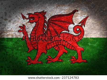 Old rusty metal sign with a flag - Wales - stock photo