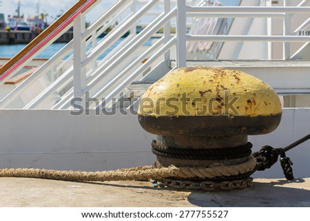 Old rusty mooring bollard at the pier. A large fragment of the dock port. - stock photo