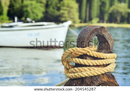 Old rusty mooring mast and ropes in nice soft light and fishing boats in the background  - stock photo