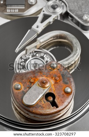 Old rusty open padlock on computer harddrive - information or data security concept - stock photo