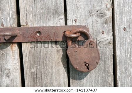 Old rusty padlock on a wooden door - stock photo