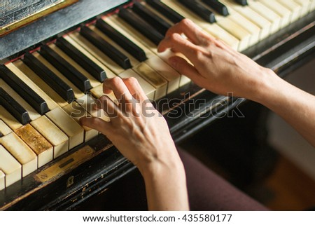 Old rusty piano, selective focus, woman's hands on keyboard - stock photo