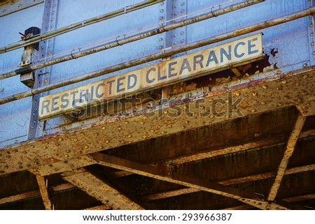 Old Rusty Railroad Overpass with Restricted Clearance Sign - stock photo