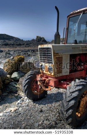 Old, rusty red and white tractor on a rocky pebble beach - stock photo