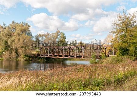 Old rusty steel bridge above river. Nikolo-Uryupino village, Moscow regon, Russia.  - stock photo
