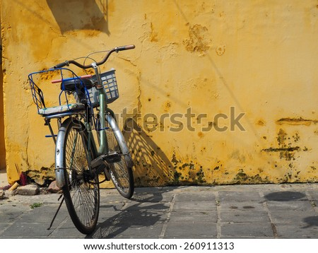 Old rusty vintage bicycle with basket near the concrete yellow wall            - stock photo