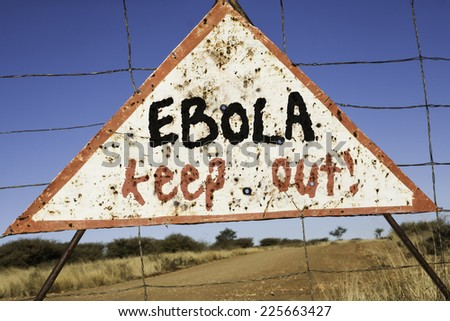 old rusty warning triangle at a fence in Africa  with the words Ebola keep out - stock photo