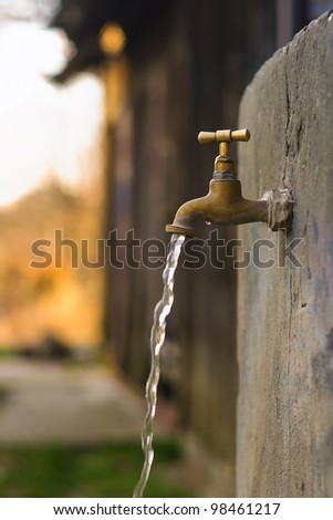 Old rusty water tap in garden - stock photo