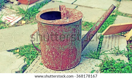Old rusty watering can in the garden - stock photo