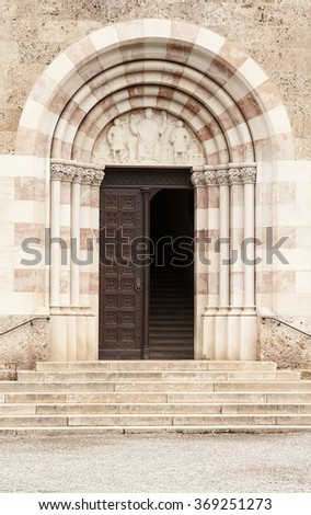 Old salt works gate, similar to a church entrance, textured door, stone arch facade with a few steps. - stock photo