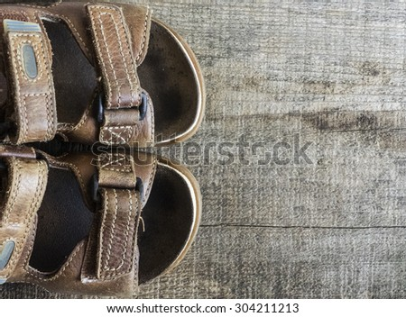 Old sandal on wood board - stock photo