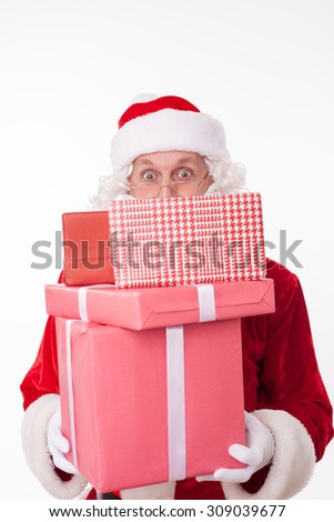 Old Santa Claus is holding presents. The heap of boxes is covering his mouth. He is standing and looking at the camera with joy. Isolated on background - stock photo