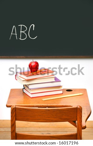 Old school desk with a stack of books and apple - stock photo