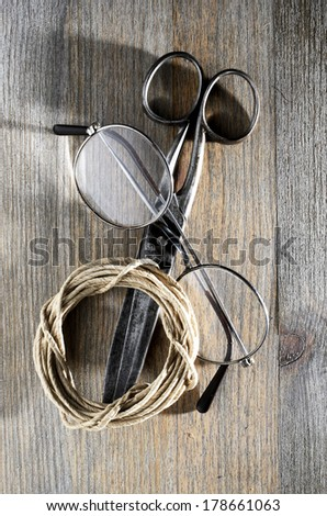 old scissors, glasses and hank of packthread over wooden background - stock photo