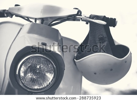 Old scooter with helmet and headlamp closeup. Vintage biker objects - romantic travel on motorbike in retro style. Monochromatic colors on stylish toned photo.  - stock photo