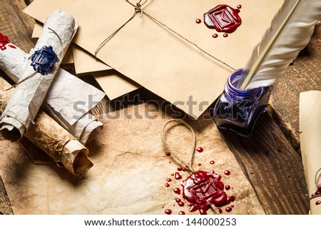 Old scrolls, sealing wax, old envelope and blue ink on wooden table - stock photo