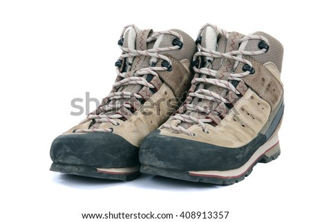 Old scuffed hiking boots on white background - stock photo