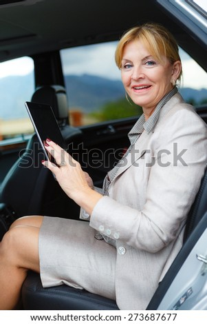 Old senior business woman 60-65 years, sitting in car, holding her Tablet PC computer and looking to camera - stock photo