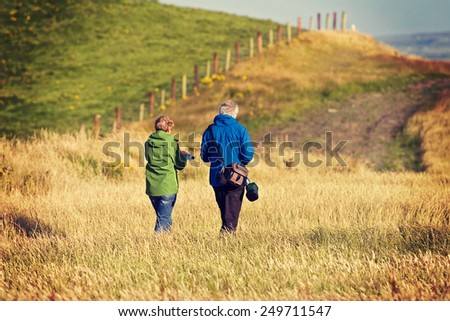 Old senior citizen couple taking a walk in the field in Ireland. Post processed with vintage filter.  - stock photo
