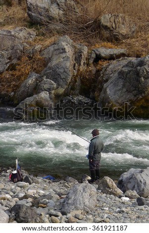 Old senior citizen fishing beside fast stream rocky river with long fishing rod - stock photo