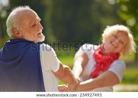 Old senior couple dancing happy together in nature - stock photo