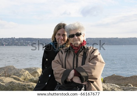 Old senior grandmother with her adult granddaughter. - stock photo