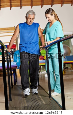 Old senior man at physiotherapy holding on to handles - stock photo