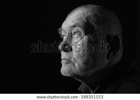 old senior man looking up in dark monochrome image - stock photo