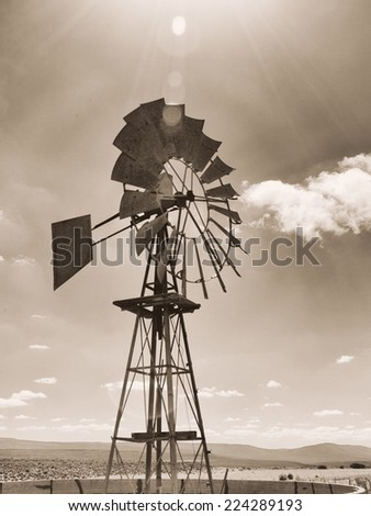 Old sepia photo of a windmill on a farm. Image is shot into the sun - stock photo