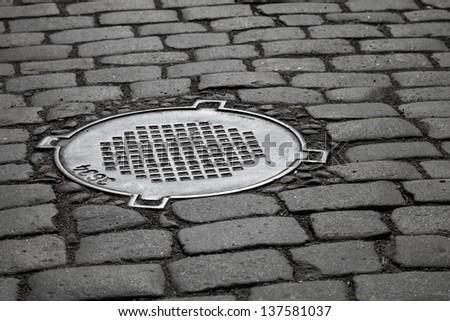 Old sewer manhole on dark cobblestone pavement - stock photo