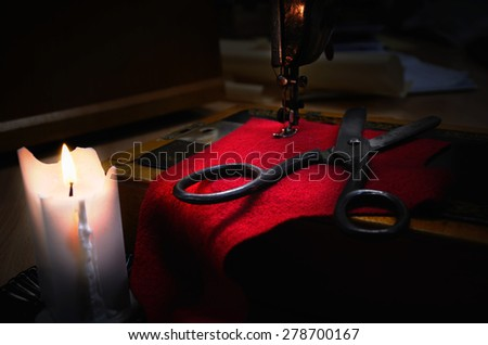 old sewing machine, fabric and rusty scissors at the light candle. horizontal, low key - stock photo