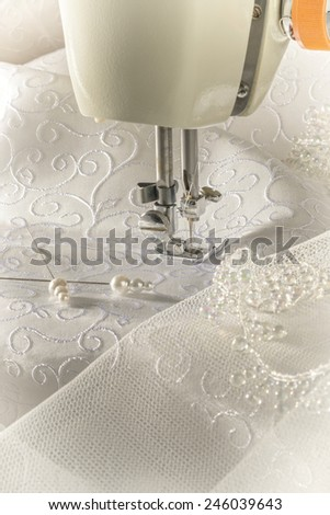 Old sewing machine with ivory fabric and pins - stock photo