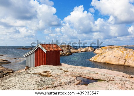 Old Shed at the rocky beach by the sea - stock photo