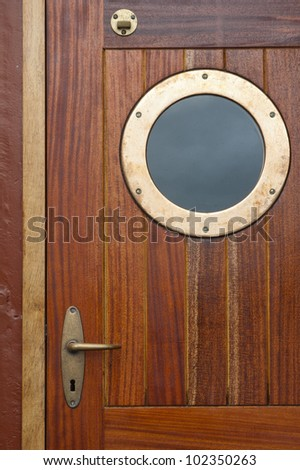 Old ship door with a window - stock photo