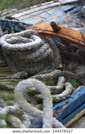 old ship's ropes and rudder - stock photo