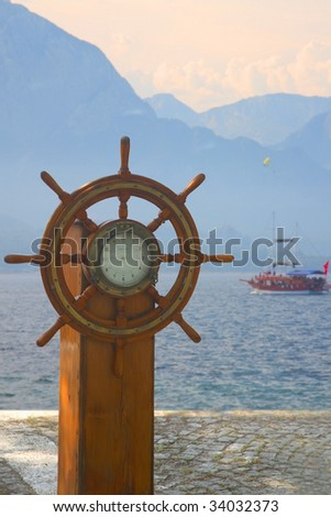 Old ship steering wheel against the sea and the yacht - stock photo
