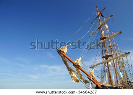 Old ship yard arm square rigging. Sailing ship's furled canvas sails and complicated rope - stock photo
