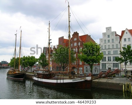 Old ships and Gothic german houses on the River Trave, Lubeck, Germany - stock photo