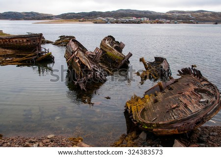 Old shipwreck in a water near the beach. Old boats in sea. - stock photo