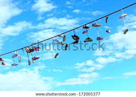 Old Shoes hanging on electrical wire against a blue sky - stock photo
