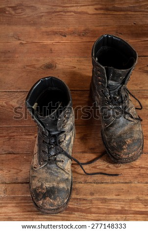 Old shoes on a wooden floor. Vintage toning - stock photo