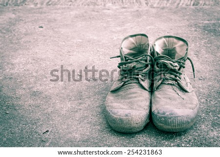 Old shoes on floor in vintage style - stock photo