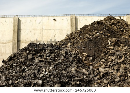 Old shredded tires on pile behind concrete wall - stock photo