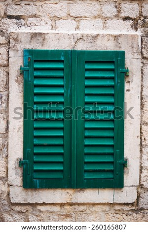 Old shutters on the windows in the old town of Kotor in Montenegro - stock photo