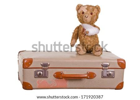 old sick teddybear on suitcase - stock photo