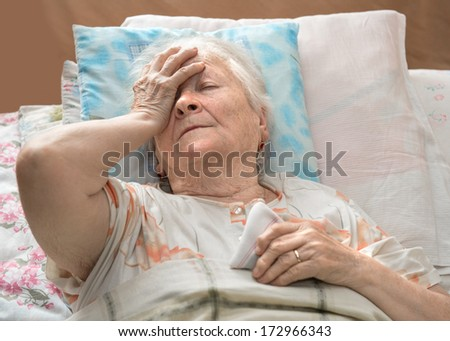 Old sick woman lying at bed - stock photo